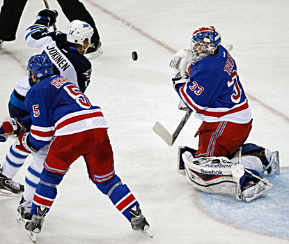 Rangers goalie Cam Talbot (right) deflects a shot by the Jets' Olli Jokinen, who scores twice in the win.  (USATSI)