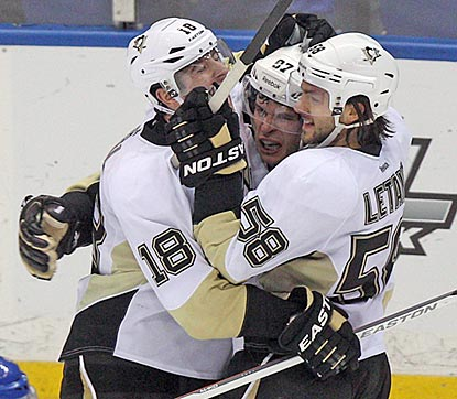 James Neal (left) and Kris Letang converge on Sidney Crosby after he scores in overtime.  (USATSI)