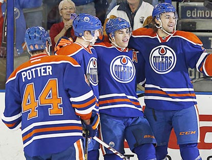Taylor Hall (third from left) celebrates with his teammates after completing his hat trick in the game's final seconds.  (USATSI)