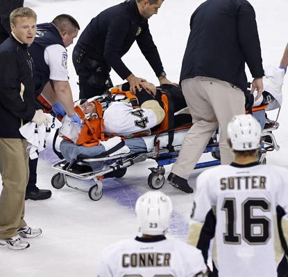 Brooks Orpik is taken off the ice on a stretcher after getting punched in the head by the Bruins' Shawn Thornton.  (USATSI)