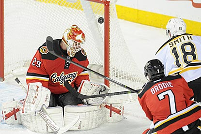 Boston's Reilly Smith lifts a shot over Calgary's Reto Berra for the winning goal late in the third period.  (USATSI)