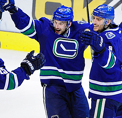 Christopher Tanev celebrates his goal with teammates as the Canucks cruise to their seventh straight victory.  (USATSI)