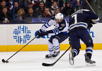 Winnipeg's Evander Kane (left), who scores a key goal late in the game, skates past Columbus's Jack Johnson.  (USATSI)