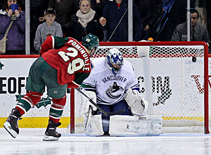 The Wild's Jason Pominville (left) scores on Canucks goalie Roberto Luongo during the shootout. (USATSI)