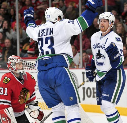 Vancouver's Daniel Sedin (right) celebrates his game-tying goal in the third period with Henrik Sedin.  (USATSI)
