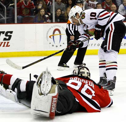 Patrick Sharp beats goalie Martin Brodeur to complete his hat trick for the Blackhawks in New Jersey.  (USATSI)