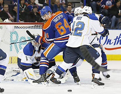 Blues goalie Brian Elliott and Oilers forward Nail Yakupov search for the puck during a scramble in the third period.  (USATSI)