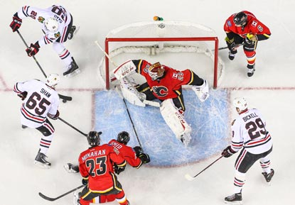 Calgary goalie Reto Berra tries to fend off Chicago's Brandon Saad (upper left), Andrew Shaw (65) and Bryan Bickell.  (USATSI)