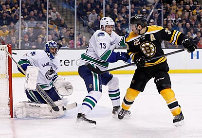 Bruins center Patrice Bergeron deflects a shot toward Canucks goalie Roberto Luongo while being defended by Alexander Edler.  (USATSI)