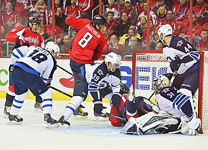 Alex Ovechkin (8) pokes in a rebound past Winnipeg goaltender Ondrej Pavelec (31) to put Washington ahead for good.  (USATSI)