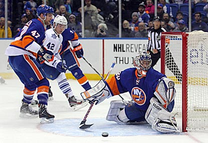 Islanders goaltender Evgeni Nabokov makes a save in the first period in front of Toronto's Tyler Bozak (42).  (USATSI)