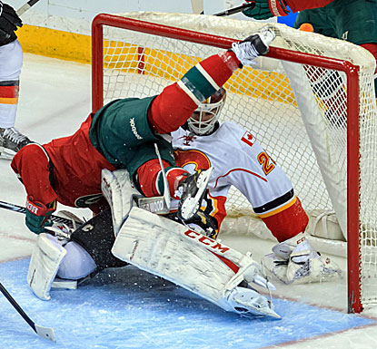 The Wild's Keith Ballard collides with Flames goalie Reto Berra during the third period of Minnesota's win. (USATSI)