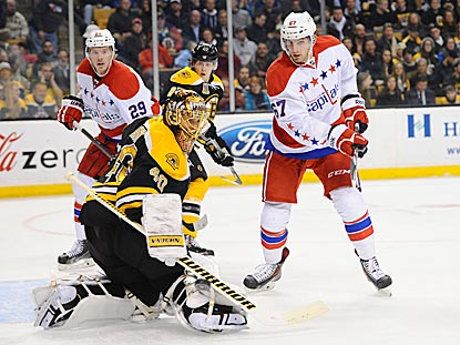 Boston's Tuukka Rask makes a save as Washington's Ryan Sloa (left) and Chris Brown close in.  (Getty Images)