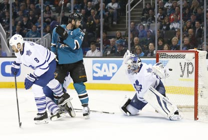 Joe Thornton (center) watches Brent Burns' shot go past Toronto goaltender James Reimer for a goal during the first period.  (USATSI)