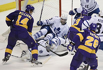 Toronto goaltender James Reimer, with some help from his teammates, denies Justin Williams (14) and the Kings a tying goal.  (USATSI)