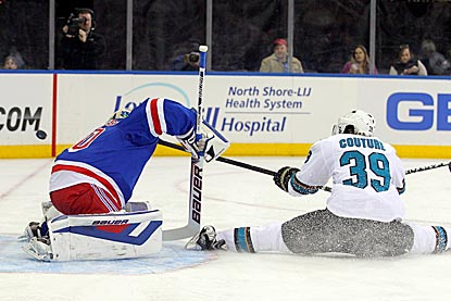 Despite the difficult position, Logan Couture puts the puck past Henrik Lundqvist to score the only goal of the game.  (USATSI)