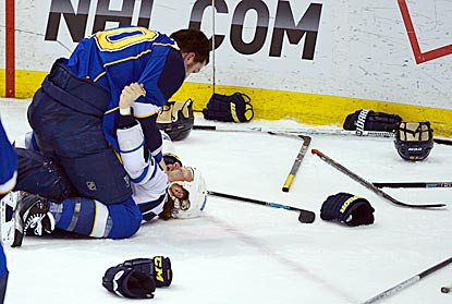 Maxim Lapierre pins down Olli Jokinen beside a littering of gloves and sticks during a game-ending line brawl.  (USATSI)