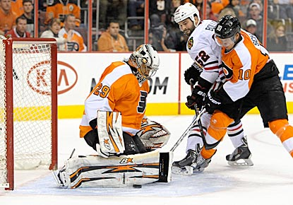 Philly's Ray Emery makes a save in overtime while teammate Brayden Schenn and Chicago's Brandon Bollig battle for position.  (USATSI)