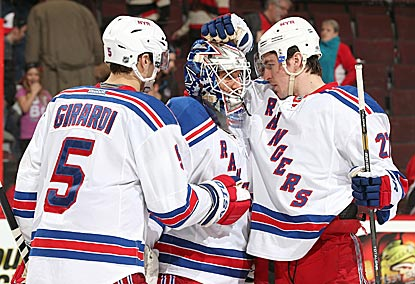 Henrik Lundqvist receives congratulations from Dan Girardi and Ryan McDonagh on his franchise-record 302nd victory.  (Getty Images)