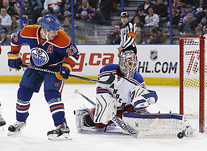 Oilers forward Matt Hendricks tips a shot just wide of the net and Rangers goaltender Cam Talbot during the third period.  (USATSI)