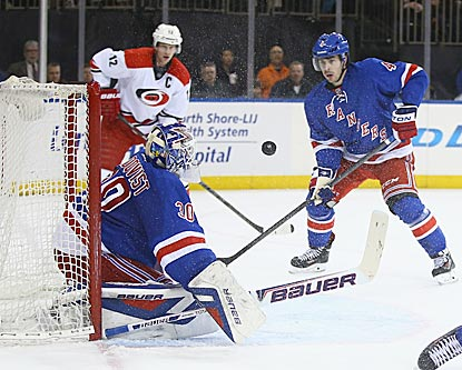 New York's Henrik Lundqvist makes a save as teammate Raphael Diaz and Carolina's Eric Staal look on.  (Getty Images)