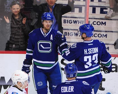 Daniel Sedin (left) accepts congratulations from twin brother Henrik after scoring one of his two first-period goals.  (USATSI)