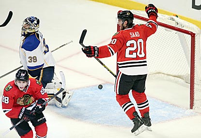 Brandon Saad celebrates while Patrick Kane skates off after scoring in overtime against Blues goaltender Ryan Miller.  (USATSI)