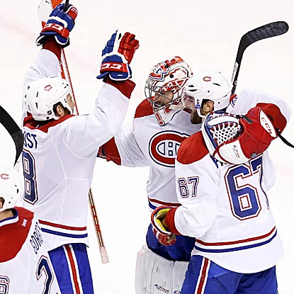 Teammates embrace Carey Price (center), who stops 55 of 56 shots in Games 6 and 7 to help lead Montreal into the East finals.  (USATSI)