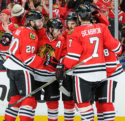 Duncan Keith draws a crowd to celebrate what proves to be the winning goal for the Blackhawks.  (Getty Images)