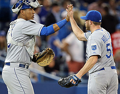 Reliever Greg Holland celebrates with Salvador Perez after Holland closes it out for his 15th save in 16 chances. (USATSI)