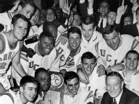 in this March 22, 1964, file photo UCLA coach John Wooden, right, and members of the Bruin team smile over victory that brought them the NCAA basketball championship trophy, March 22, 1964, Kansas City, Mo. UCLA downed the Duke University team, 98 to 83, in the final game to complete their season with 30 straight wins. Players in front row are, from left: Gail Goodrich, Walt Hazzard and Jack Hirsch, holding trophy. Man directly behind Hirsch and Coach Wooden is Keith Erickson. Wooden, college basketball's gentlemanly Wizard of Westwood who built one of the greatest dynasties in all of sports at UCLA and became one of the most revered coaches ever, has died. He was 99. (AP Photo, File)