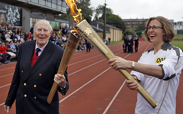British running legend Roger Bannister passes the flame on to Oxford student Nicola Byrom. (AP)