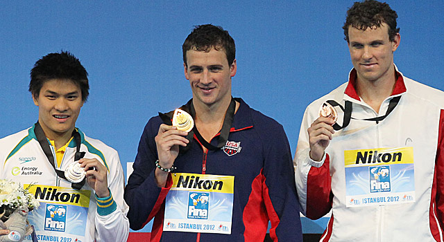 Ryan Lochte (center) poses with his gold after the 100-meter individual medley. (AP)