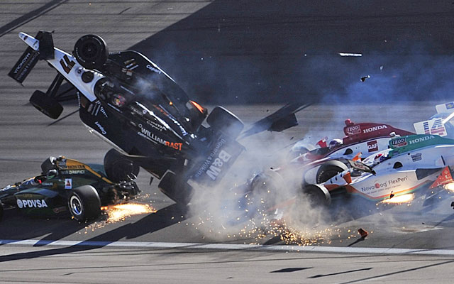 Dan wheldon s car goes airborne before striking the fence leading to