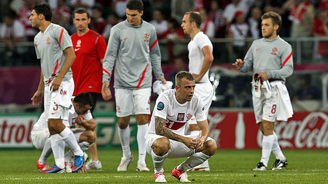 Polish players are dejected after the co-host nation is eliminated in the group stage. (AP)