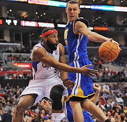 Warriors center Andris Biedrens blocks the pass of guard Baron Davis on Saturday in Los Angeles. (US Presswire)