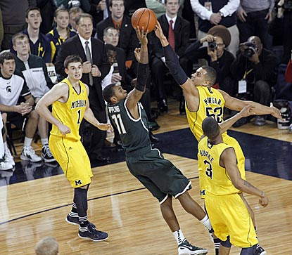 Michigan State's Keith Appling shoots over Jordan Morgan in the final seconds. That shot and an MSU follow don't go in.  (AP)